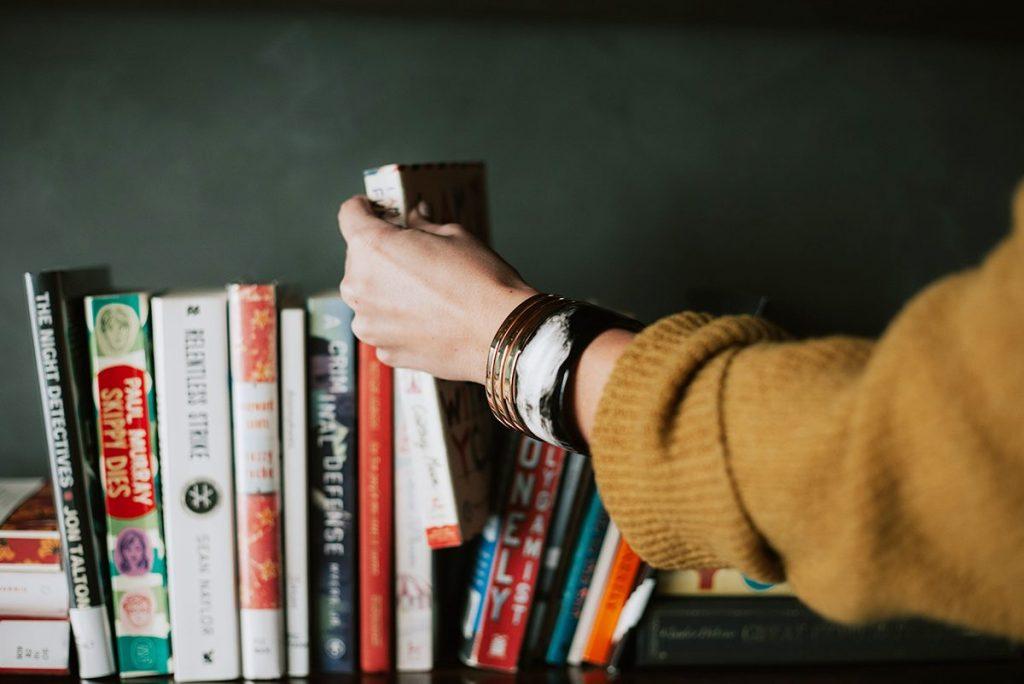 本棚から本を取り出す手